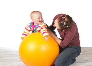 Devoted mother exercising her laughing baby who has late development of motor activity using a yellow pilates ball