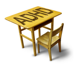 ADHD Concept for hyperactivity disorder and attention deficit behavior as a school desk with the letters carved into the wooden table as a healthcare symbol for childhood mental health issues.